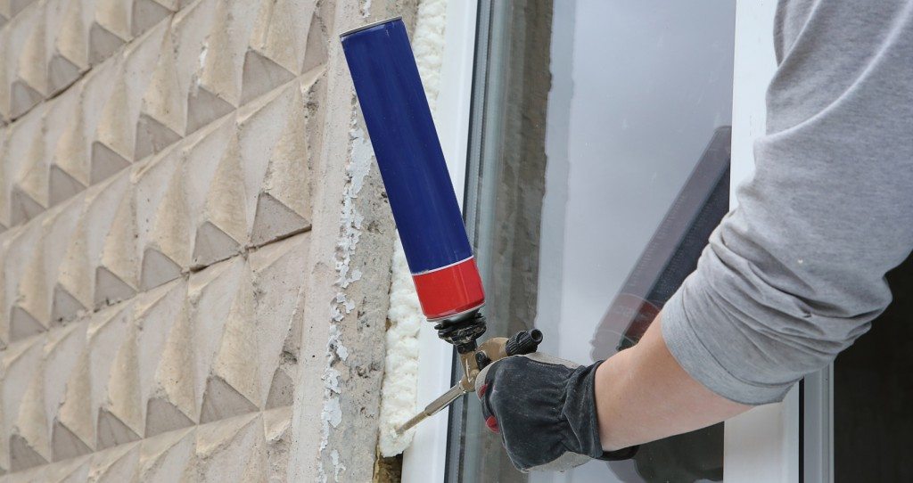 Worker's hand fix a window using polyurethane foam