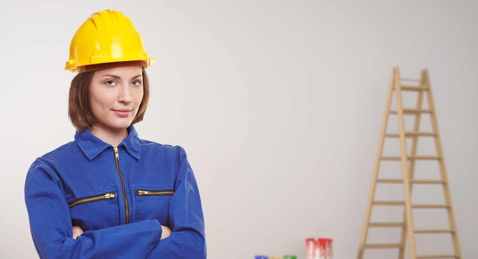 Frau als Handwerker bei Renovierung in einem leeren Zimmer mit Leiter